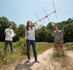 Students doing research in a field with a large antenna